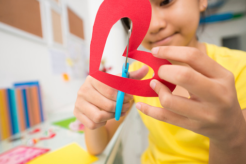 Girl cutting out paper heart, selective focus