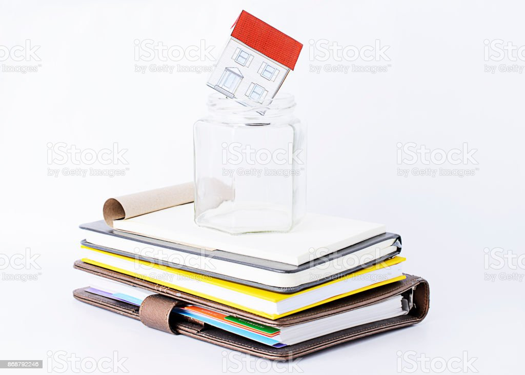 Paper home into empty glass on books stack stock photo