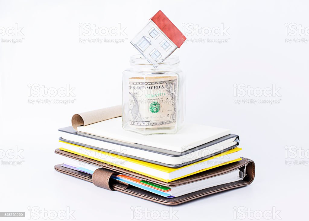 Paper home into glass saving on books stack stock photo