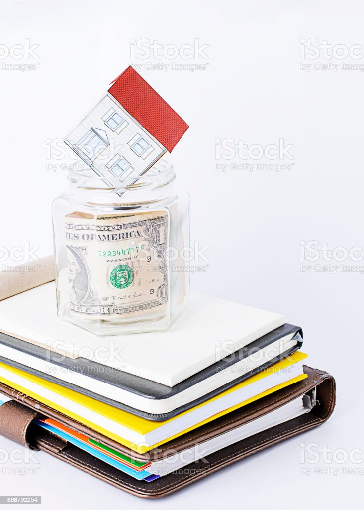 Paper home into glass saving on books stack vertocal backgrounds stock photo
