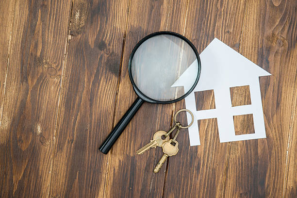 paper house and key with Magnifying Glass, House hunting stock photo