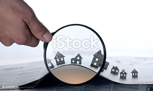 istock Paper house under a magnifying lens 610453820
