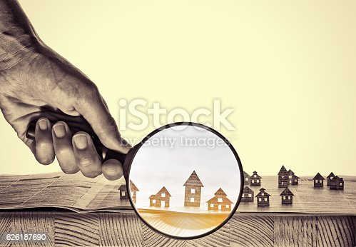 626187670istockphoto Paper house under a magnifying lens 626187690