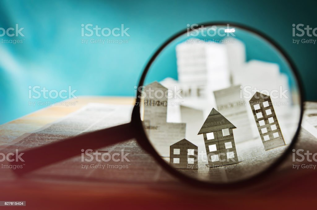 Paper house under a magnifying lens stock photo