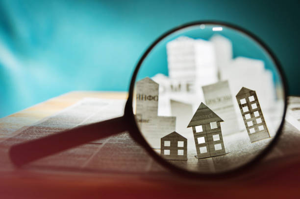 Paper house under a magnifying lens Magnifying glass in front of an open newspaper with paper houses. Concept of rent, search, purchase real estate. information equipment stock pictures, royalty-free photos & images