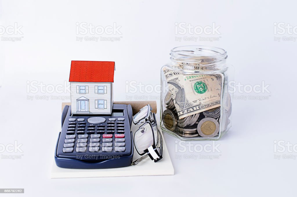 Paper house with calculator and glasses and bottles saving money stock photo