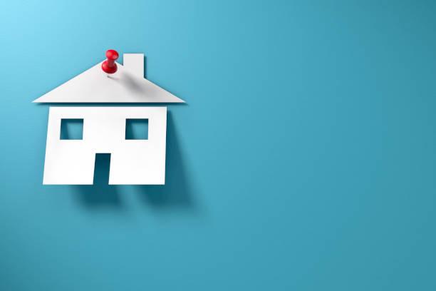 papierhaus mit daumendrücken auf blauem hintergrund immobilienkonzept - immobilienangebote stock-fotos und bilder