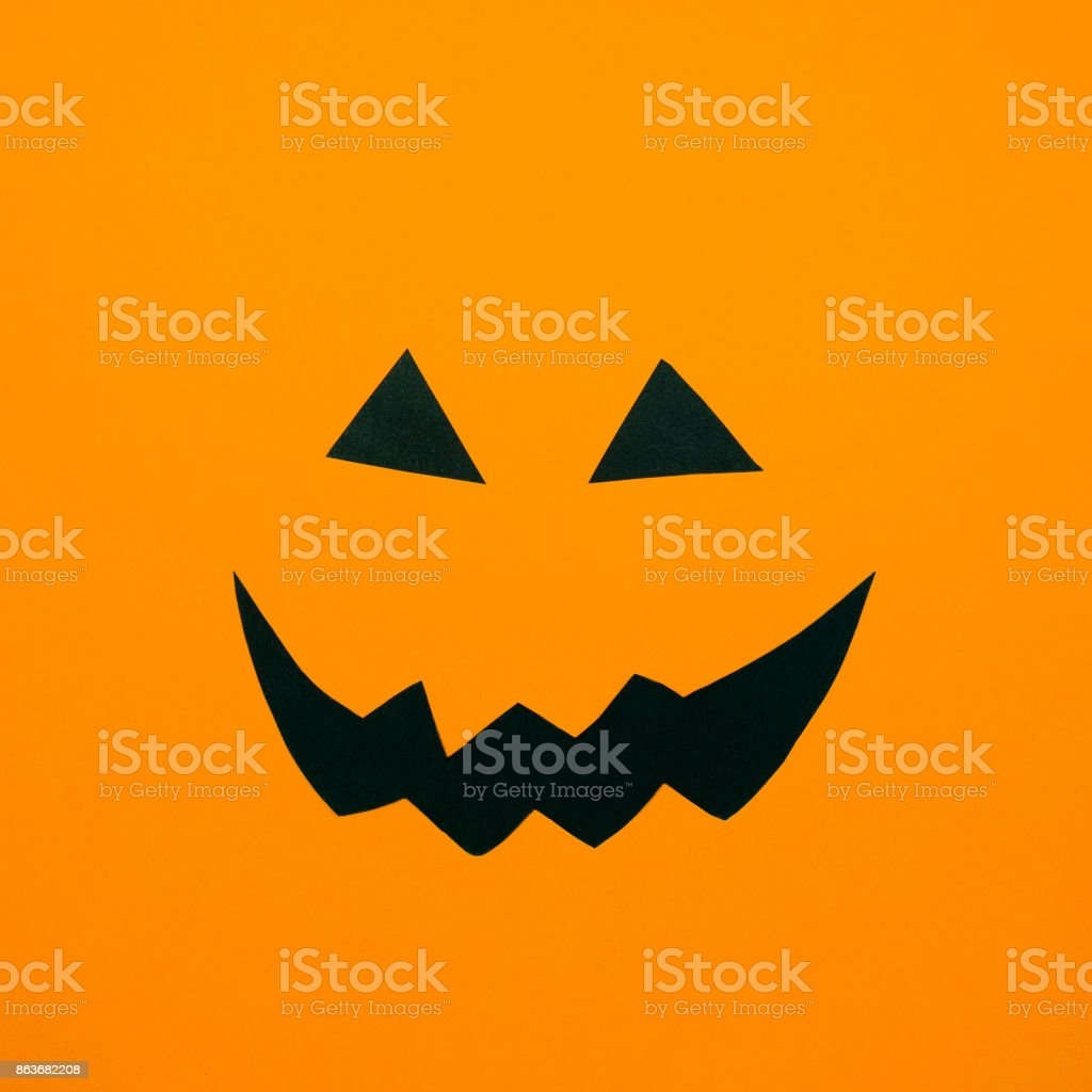 Paper Jack O'Lantern face on orange background. Halloween concept. Flat lay stock photo