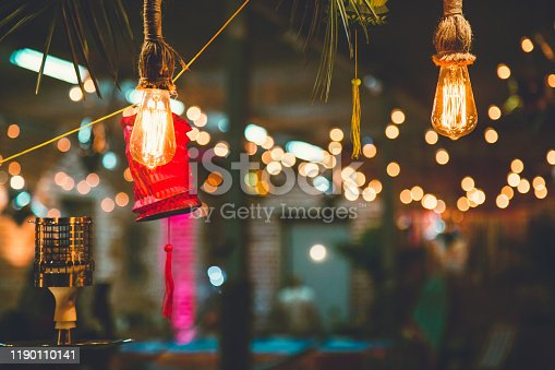Colorful paper lanterns and bulbs hanging as a party decor. Night party.