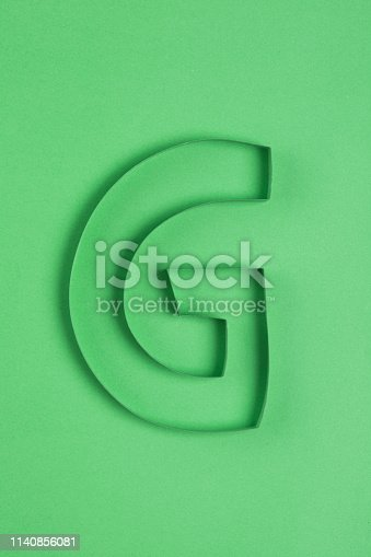 Paper  letter G on green background