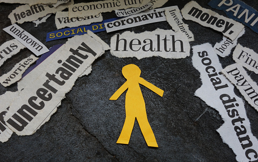 Paper man cutout surrounded by Corona Virus and economic news headlines
