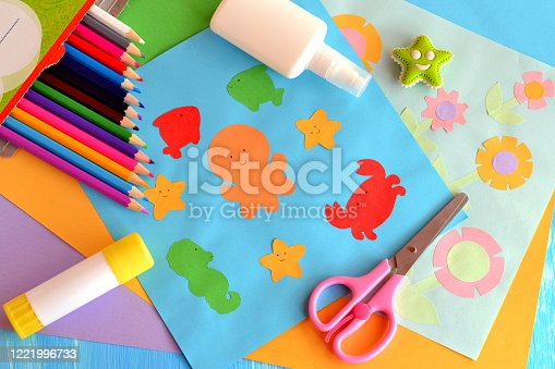 istock Paper marine animals and flowers cards. Sheets of colored paper, scissors, pensils, glue stick on a wooden background. Summer paper crafts for kids to make at home or in kindergarten 1221996733