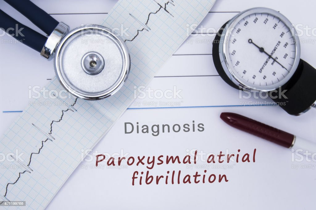 Paper medical release form with diagnosis Paroxysmal atrial fibrillation from category Cardiac arrhythmia diseases with ECG and stethoscope. Medical report of cardiologist or doctor internal medicine stock photo