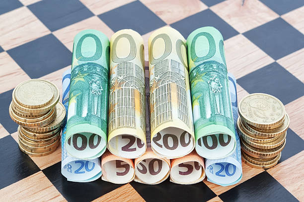 Paper money and coins as the euro on chessboard. stock photo