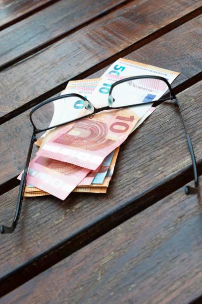 Papier Geld am Tisch mit Lesebrille – Foto