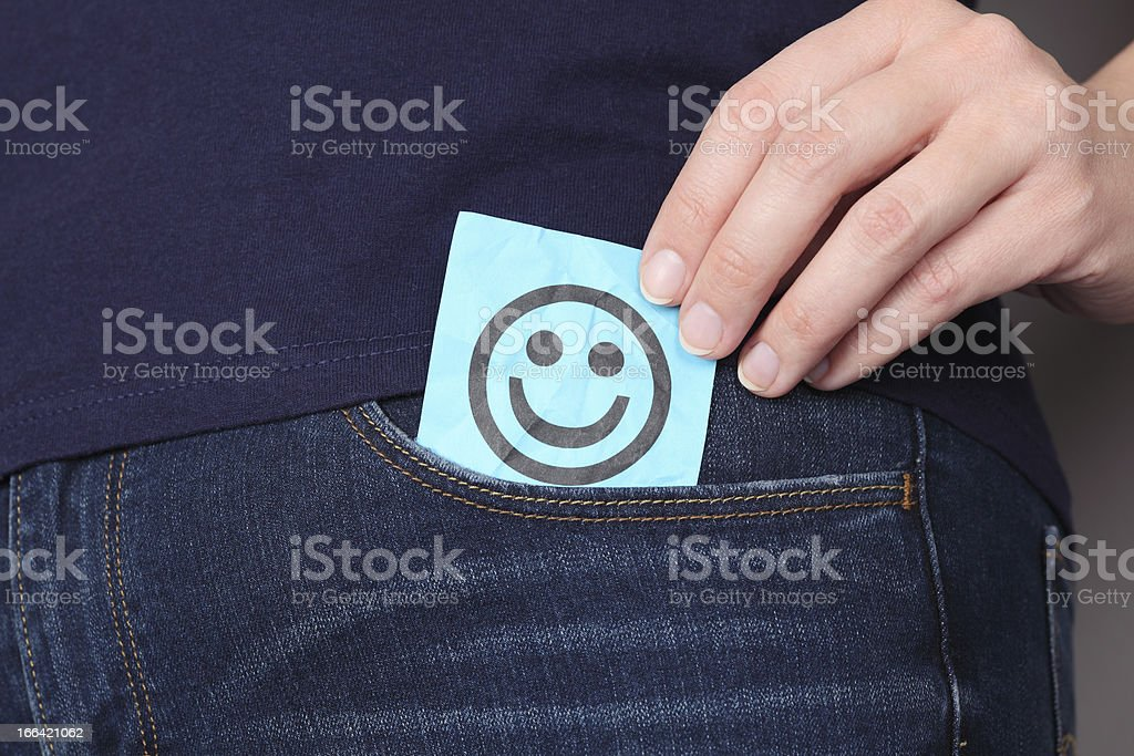Paper note with smiling face in pocket of jeans royalty-free stock photo