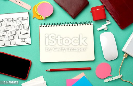 istock paper notebook, keyboard, power bank with cable, red smartphone with blank black empty screen 1214799972