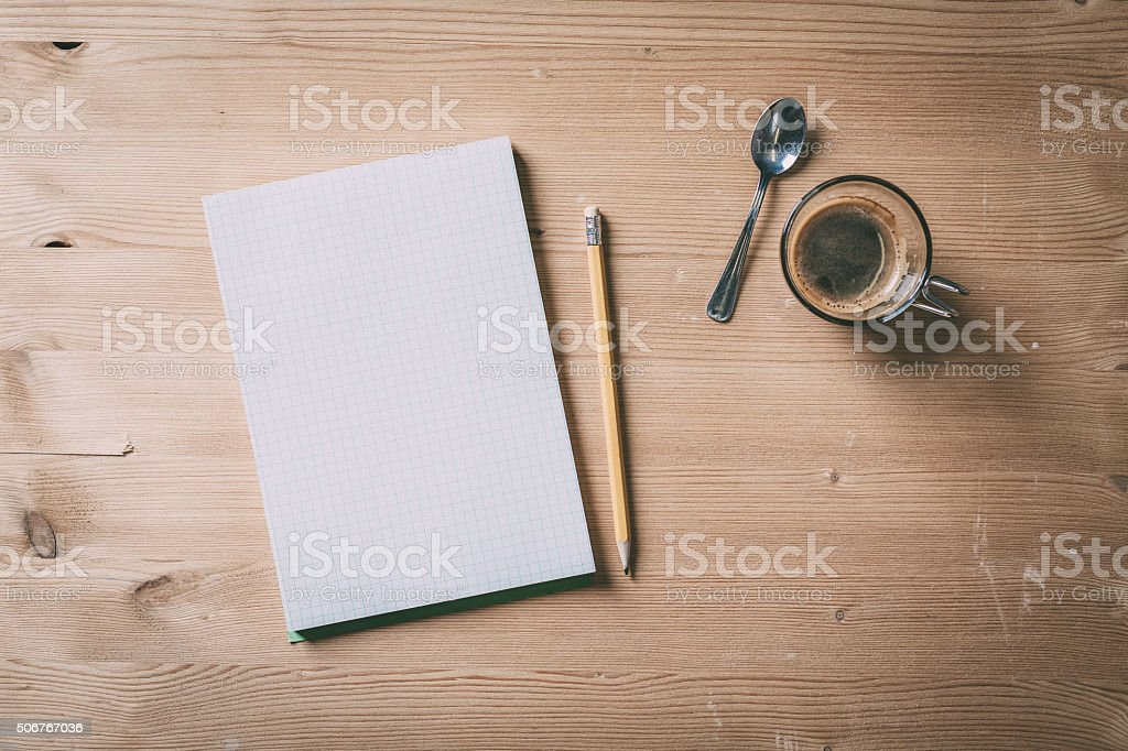Paper notebook with pencil and coffee on a wood table stock photo