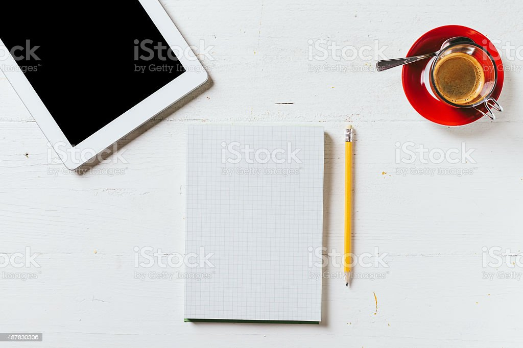 Paper notebook with pencil, coffee and tablet on wood table stock photo