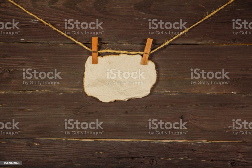 Paper old notebook on a rope on a black wooden board. Place for text. Copy space. Place for announcements. stock photo