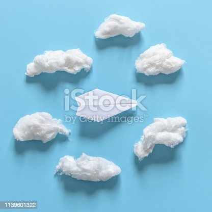 istock Paper origami plane among white clouds on blue background. 1139601322