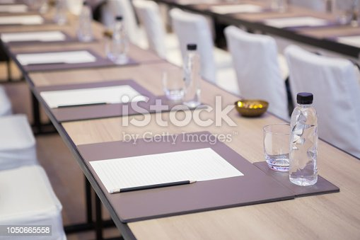 istock Paper, pencil, water bottle, glass on the table in the seminar room background 1050665558