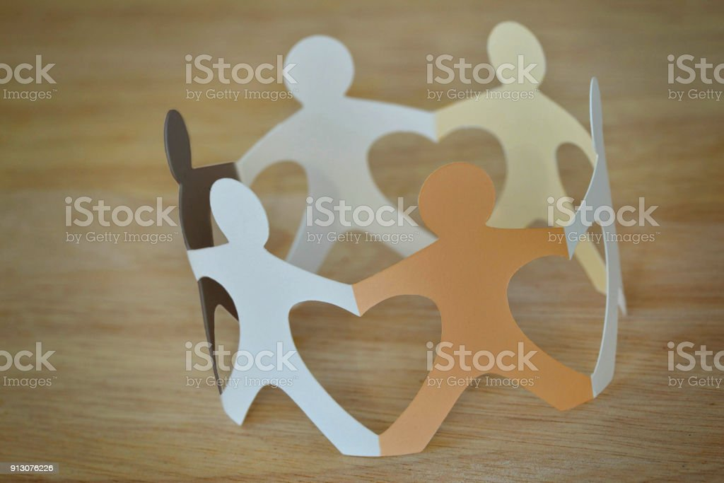 Paper people in a circle holding hands - Anti-racism and love concept stock photo