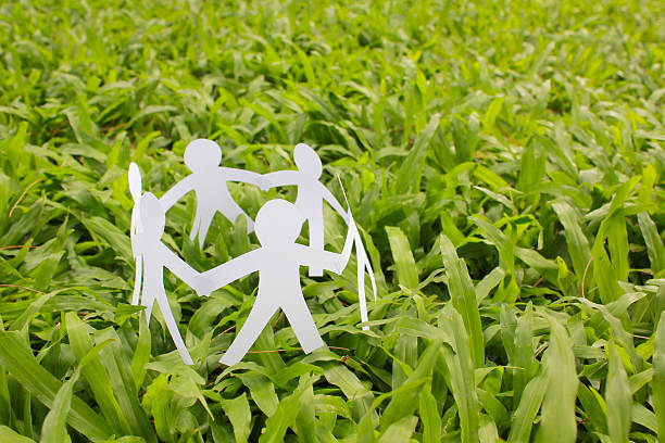 paper people in a circle with green grass background - écologiste rôle social photos et images de collection
