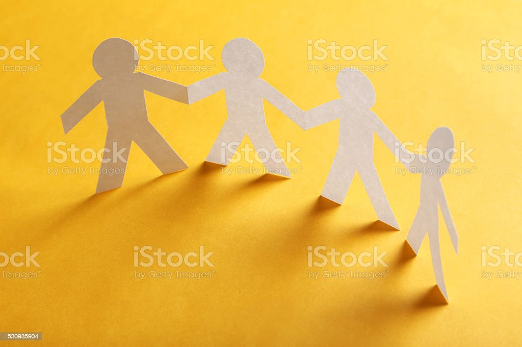 Paper people on the orange paper background stock photo