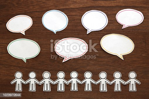 istock Paper people  with colorful blank dialog speech bubbles on brown wood.  Communication concept. 1023970544