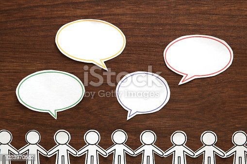 istock Paper people  with colorful blank dialog speech bubbles on brown wood.  Communication concept. 1023970552