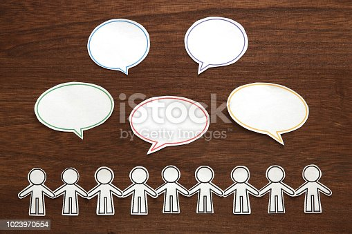 istock Paper people  with colorful blank dialog speech bubbles on brown wood.  Communication concept. 1023970554