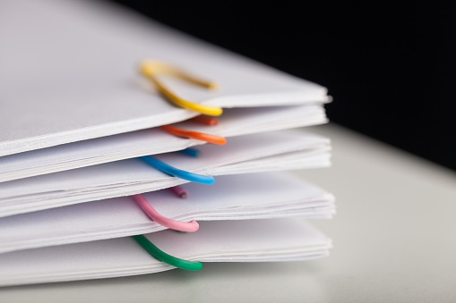File folders with documents and bright paperclips