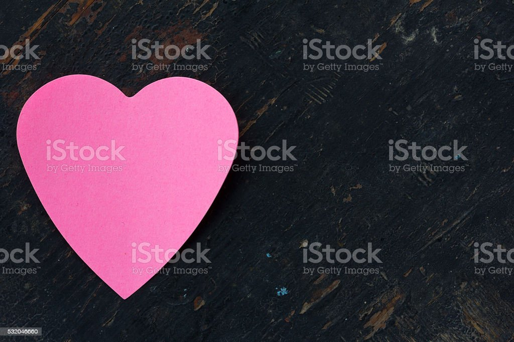 Valentine - paper pink heart against a black wooden background. Copy...