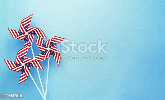 Paper pinwheels textured with American flag on blue background. Horizontal composition with copy space. Front view. 4th of July concept.