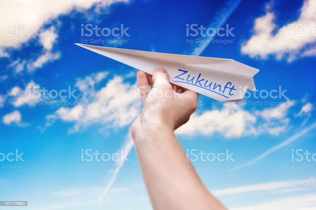 Paper Plane Against A Blue Sky With The German Word For Future As A