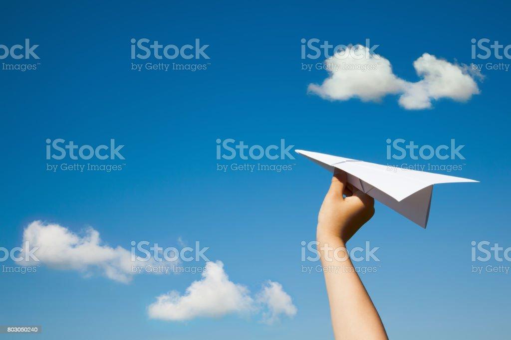 Avion de papier dans la main de l'enfant. - Photo