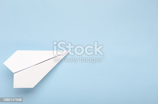 istock Paper plane on a blue background. Concept of flight, travel, transfer. Top view, copy space, flat lay 1065147536