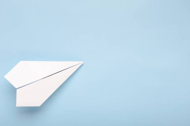 paper plane on a blue background. concept of flight, travel, transfer. top view, copy space, flat lay - paper airplane stock photos and pictures