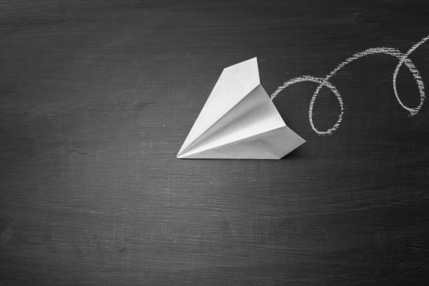 Paper plane on blackboard background stock photo