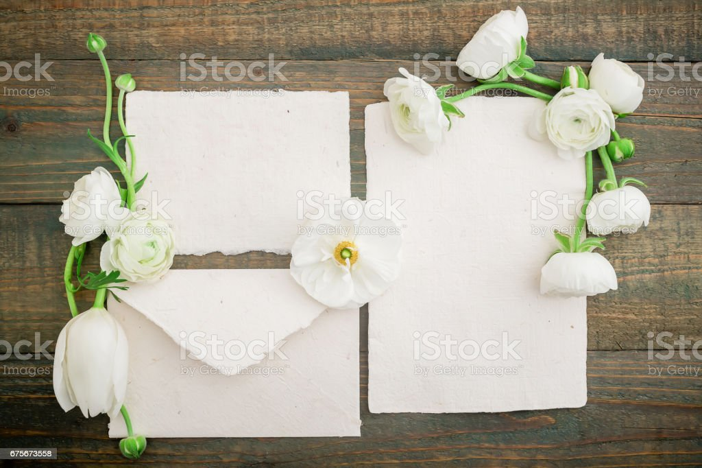 Paper post cards, envelope and white flowers on wood background. Flat lay, top view. Vintage background. royalty-free stock photo