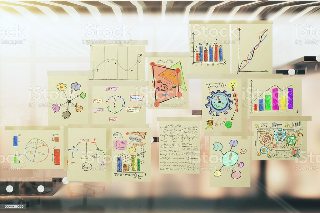 Paper posters with notes and schemes on glassy wall stock photo