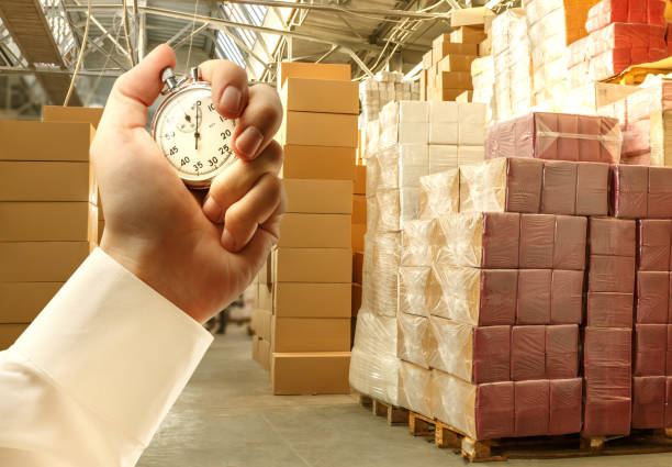 Paper products storehouse and stopwatch in hand stock photo