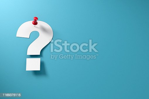 Paper question mark on blue paper background and red thumbtack.