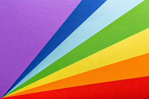 Paper rainbow colored rays stripes background. Pride concept. The basis for a greeting card with copy space.