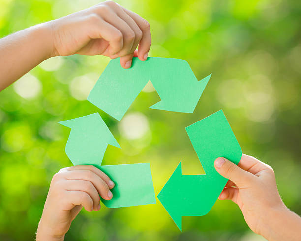 paper recycle sign in children`s hands - recycling symbol stock photos and pictures