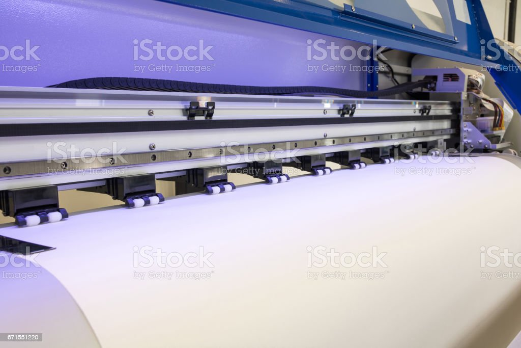 Paper roll in large printer format inkjet machine for industrial business. stock photo