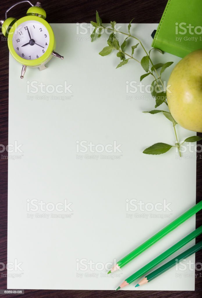 Paper sheet, clock, pencils, mint and apple on dark wooden background. stock photo