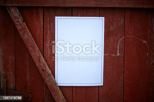 924754302istockphoto paper sheet on red wall 1097419788