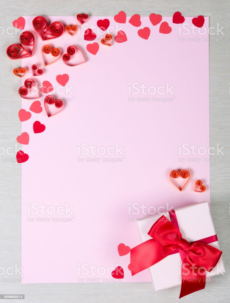 Paper sheet surrounded by handmade paper hearts and fancy box stock photo
